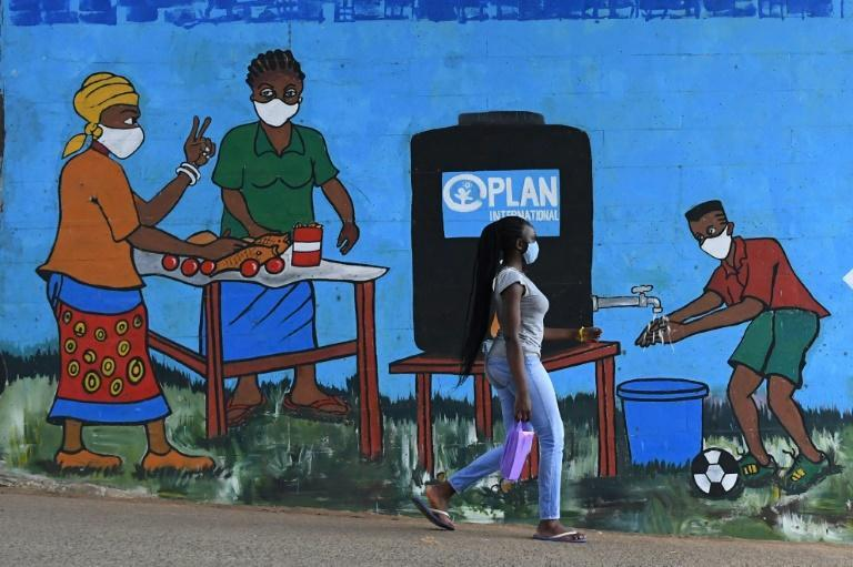 A woman with a face mask walks past graffiti that promotes hand washing and wearing face masks in Nairobi