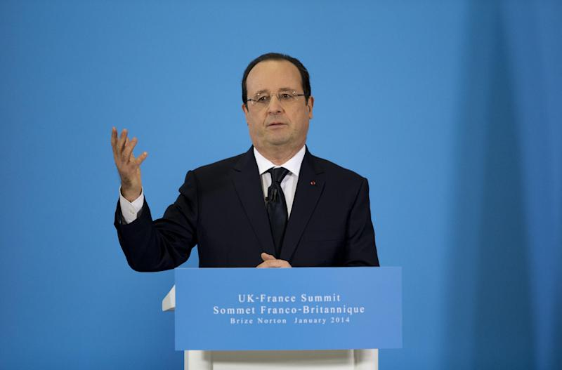 French President Francois Hollande speaks as he holds a press conference with British Prime Minister David Cameron during their one-day summit at the RAF Brize Norton air base in Brize Norton, England, Friday, Jan. 31, 2014. The one-day summit covered military cooperation, including talks over armed drones, anti-ship missiles, and underwater mine detectors, as well as a joint Franco-British force of 10,000 soldiers due to be formed in the next few years. (AP Photo/Matt Dunham)