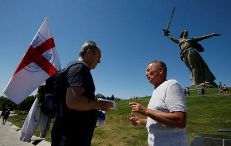 "England's fans talk in front of ""The Motherland Calls"" monument at the Mamayev Kurgan World War Two memorial complex in Volgograd, Russia June 18, 2018. REUTERS/Gleb Garanich"