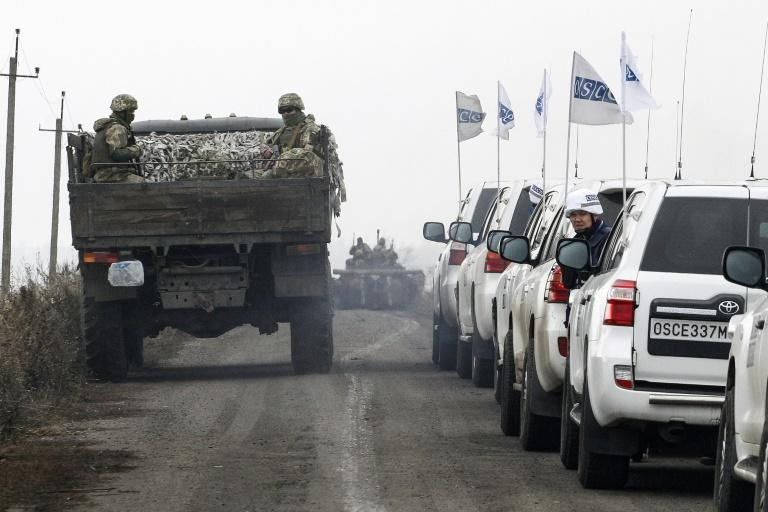 Ukrainian troops withdraw from conflict-riven Donetsk on Saturday, watched by OSCE monitors (AFP Photo/-)
