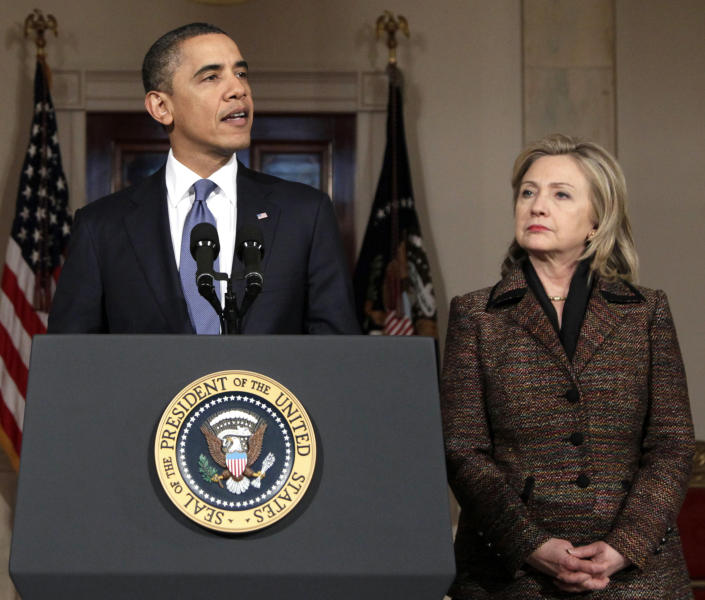 FILE - In this Feb. 23, 2011, file photo President Barack Obama, with Secretary of State Hillary Rodham Clinton at right, speaks about Libya in the Grand Foyer of the White House in Washington. Obama now has a freer hand to deal with a world of familiar problems in fresh ways. That could mean tougher Iran and Syria policies, or new engagement toward countries such as Cuba and North Korea. He could also refocus on the moribund Middle East peace efforts. But a pressing task is assigning a new national security team. Clinton has announced her plans to retire and could stay a few weeks past January to help the administration as it reshuffles personnel. (AP Photo/Carolyn Kaster, File)