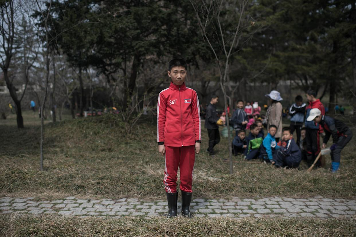 "Kim Hyun-U, 12, poses for a portrait as he takes part in a seasonal initiative referred to as a ""do good things"" campaign, in which residents are encouraged to sweep and tidy the city, in a park in Pyongyang."