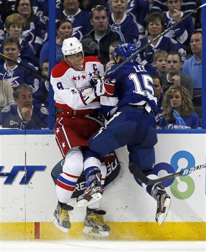 Washington Capitals' Alex Ovechkin, left, of Russia, is checked by Tampa Bay Lightning's Brian Lee during the second period of an NHL hockey game Monday, April 2, 2012, in Tampa, Fla. (AP Photo/Mike Carlson)