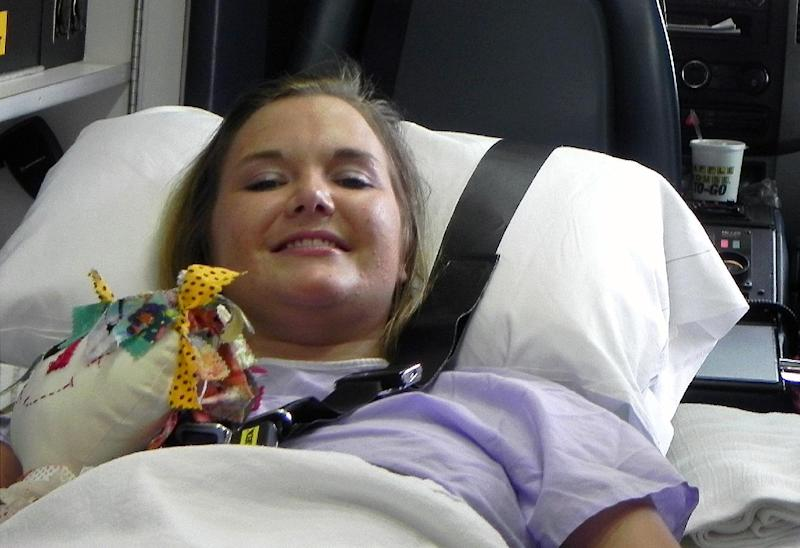 FILE - In this Monday, July 2, 2012 file photo provided by Andy Copeland, Aimee Copeland smiles as she leaves a hospital in Augusta, Ga., headed for an inpatient rehabilitation clinic. Copeland, who lost both hands, her left leg and right foot after contracting a flesh-eating disease, was on her way back from Ohio, on Friday, May 17, 2013 after being fitted with prosthetic hands. (AP Photo/Courtesy of Andy Copeland, File)