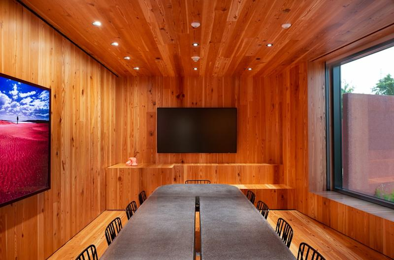 The Jewel Box room, for meetings and special events, is wrapped in pine and decorated with a polished concrete table with chairs, all designed by Adjaye.