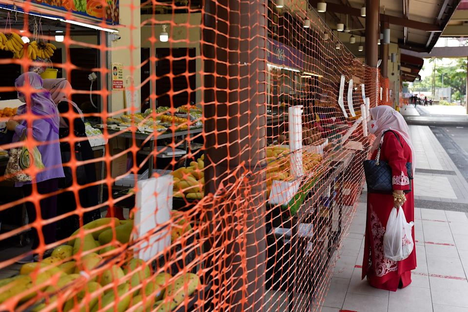 A wet market is cordoned off to limit entry and exit points after a surge in the number of coronavirus disease (COVID-19) cases in Singapore July 23, 2021. REUTERS/Caroline Chia