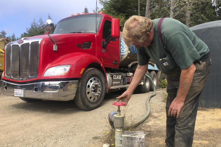 """Brian Clark fills his water truck in Little River, Calif., on Wednesday, Aug. 4, 2021. Tourists flock to the picturesque coastal town of Mendocino for its Victorian homes and cliff trails, but visitors this summer will also find public portable toilets and dozens of signs on picket fences announcing the quaint Northern California hamlet: """"Severe Drought Please conserve water."""" Clark has been selling water from his well outside of town and trucking it to the people who need it, but he said he can't keep up with the demand. (AP Photo/Haven Daley)"""
