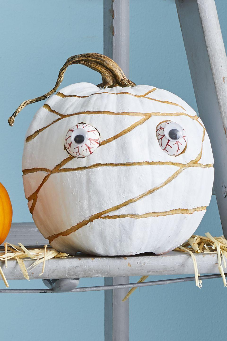 """<p>Though this cool little design does require a little cutting, it's not technically carving. Start by painting your pumpkin white (unless you bought a white pumpkin, in which case, go onto the next step). Draw any sort of wrap design on it, and then etch the lines with a linoleum-cutting tool. Glue googly eyes onto a couple Ping-Pong balls and draw red veins. Finally, cut out the eye sockets so that the balls fit inside of it. </p><p><a class=""""link rapid-noclick-resp"""" href=""""https://www.amazon.com/Ping-Pong-Balls-White-2-Pack/dp/B01DWL911W?tag=syn-yahoo-20&ascsubtag=%5Bartid%7C10070.g.331%5Bsrc%7Cyahoo-us"""" rel=""""nofollow noopener"""" target=""""_blank"""" data-ylk=""""slk:SHOP PING PONG BALLS"""">SHOP PING PONG BALLS</a></p>"""