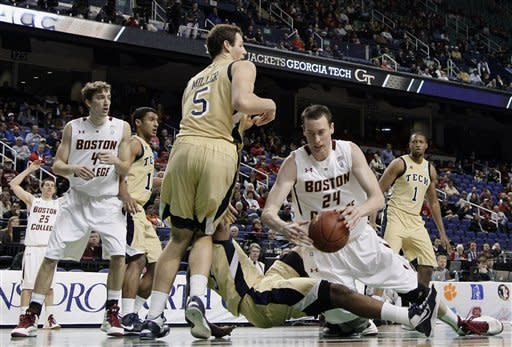 Boston College's Dennis Clifford (24) falls as he drives against Georgia Tech's Marcus Georges-Hunt (3) and Daniel Miller (5) during the first half of an NCAA college basketball game at the Atlantic Coast Conference tournament in Greensboro, N.C., Thursday, March 14, 2013. (AP Photo/Gerry Broome)