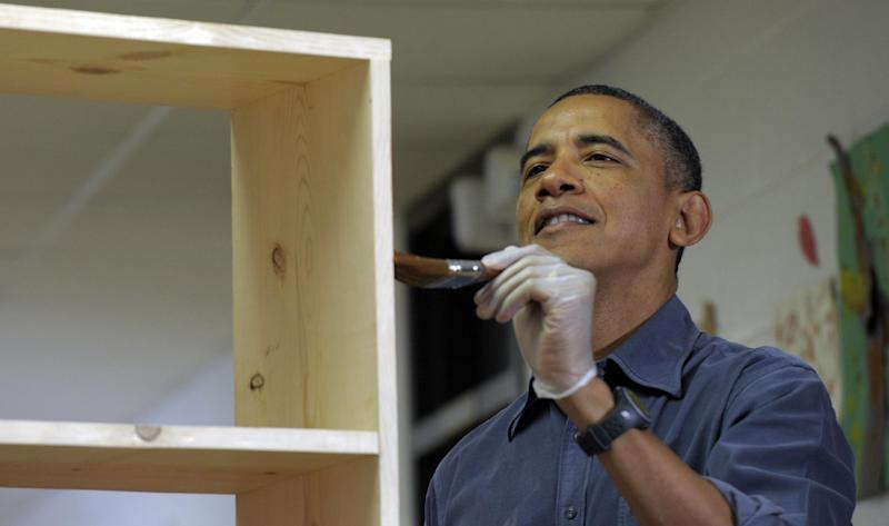 President Barack Obama stains a bookshelf at Burrville Elementary School in Washington, Saturday, Jan. 19, 2013, as the first family participated in a community service project for the National Day of Service, part of the 57th Presidential Inauguration. (AP Photo/Susan Walsh)