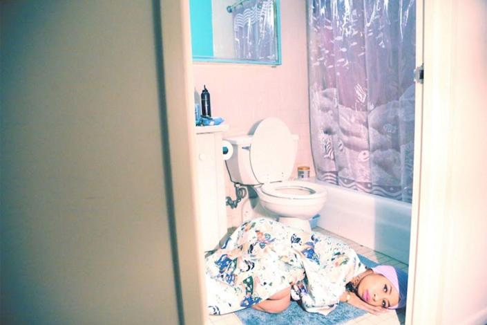 """<p><strong>Mourning Sickness</strong></p><p>I produced this and the photo """"Kia and Mommy"""" on the same day. I was feeling very creative. I wanted the first image to be in my bathroom because I wanted to talk about something really personal. It's about the side-effects of the HIV medication that I have to take, especially when I change it up. It's thinking about my experience in high school, when I was sick in the mornings before class. I wanted to look at it like a Disney cartoon, or something theatrical. It was also a play on the word 'mourning' because when I lost my mother I spent a lot of time on the floor of that bathroom, crying. </p><span class=""""copyright"""">Photographs: Courtesy of Kia LaBeija.</span>"""