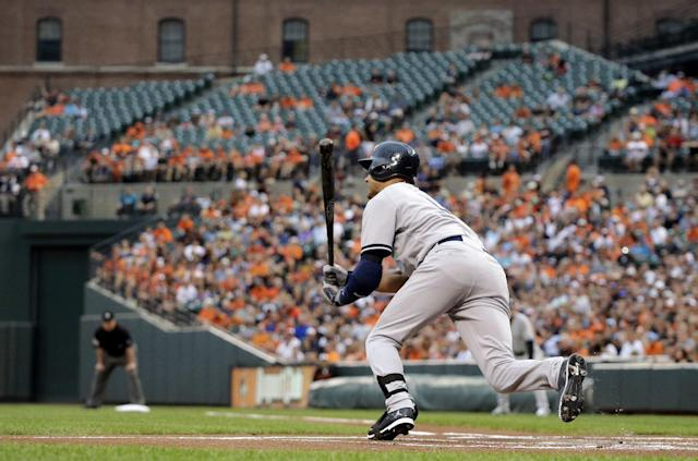 New York Yankees' Derek Jeter hits a sacrifice ground ball in the first inning of a baseball game against the Baltimore Orioles, Monday, Aug. 11, 2014, in Baltimore. Brett Gardner scored on the play. (AP Photo/Patrick Semansky)
