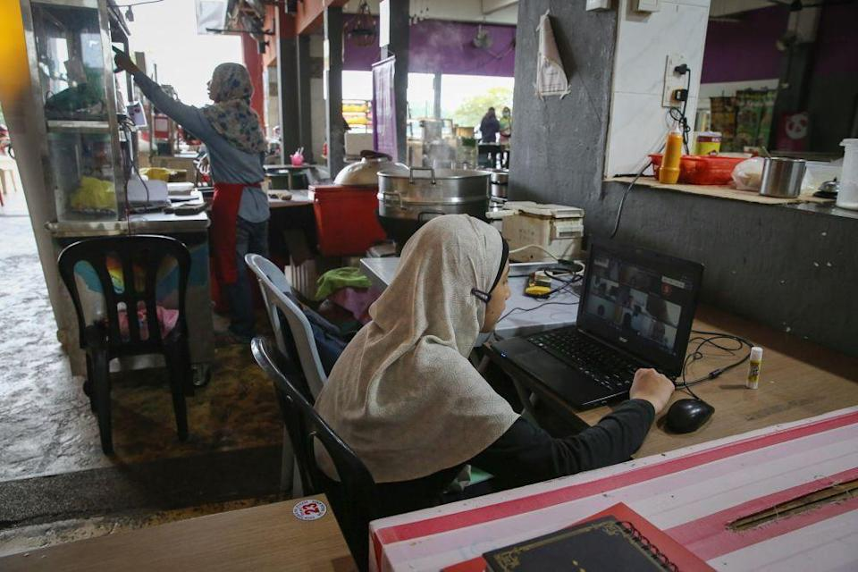 Alya Khadeeja Mohd Zaidi, a Form One school student, takes part in an online class near her mother's food stall in Shah Alam amid movement control order January 20, 2021. — Picture by Yusof Mat Isa