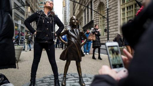 Women are growing in the fund management industry, but their numbers are still well behind men. PHOTO: A girl poses with the Fearless Girl State in Manhattan. She's at least safe until International Women's Day on March 8.