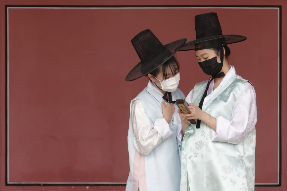Women wearing face masks to help protect against the spread of the new coronavirus watch a mobile phone at the Gyeongbok Palace, one of South Korea's well-known landmarks, in Seoul, South Korea, Saturday, July 25, 2020. South Korea reported newly confirmed cases of COVID-19 over the past 24 hours, its first daily jump over 100 in nearly four months. (Photo/Ahn Young-joon)