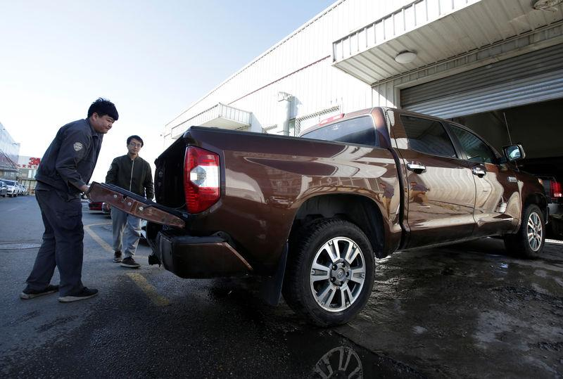 A worker closes the back of a Toyota Tundra pickup truck at Pickup Fan Club, on the outskirts of Beijing