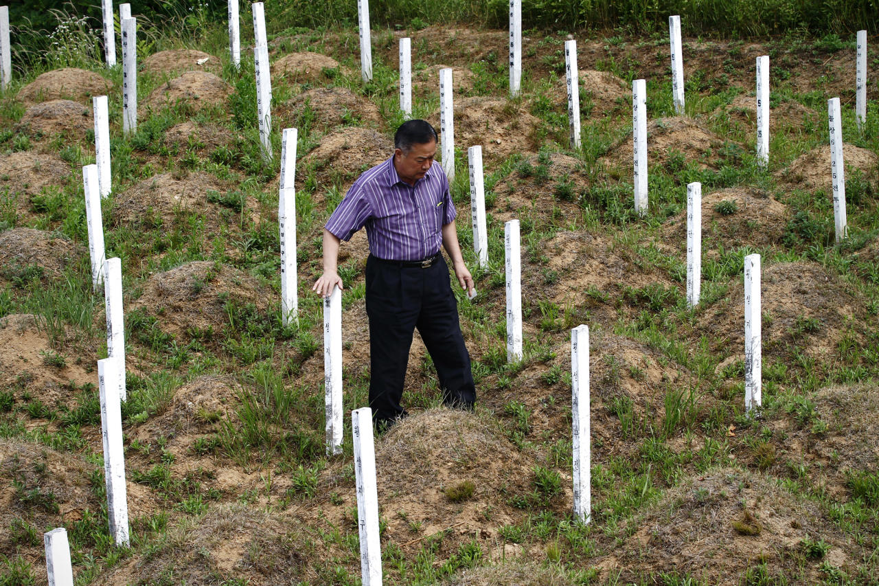 """In this Thursday, June 28, 2012 photo, local resident Kim Dong-hun inspects the wooden grave markers at the """"enemy cemetery,"""" where Chinese and North Korean soldiers who died in the Korean War are buried, just south of the Demilitarized Zone in Paju, South Korea. Hundreds of identical wooden grave markers stand on the hill surrounded by rice paddies and trees, North Korea's dark mountains visible in the distance. They call this the """"enemy cemetery,"""" though of the two nations whose soldiers are buried here, only North Korea is still considered an enemy by the South. The other, China, has inspired proposals for improving this site, but bitter feelings for the North have formed a seemingly impassable barrier. (AP Photo/Hye Soo Nah)"""