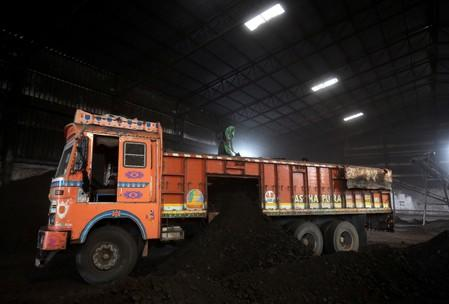 FILE PHOTO: Worker shovels coal in a supply truck at a yard on the outskirts of Ahmedabad