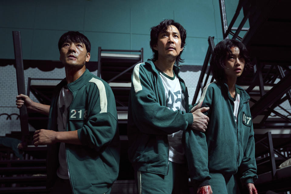 """This undated photo released by Netflix shows South Korean cast members, from left, Park Hae-soo, Lee Jung-jae and Jung Ho-yeon in a scene from """"Squid Game."""" Squid Game, a globally popular South Korea-produced Netflix show that depicts hundreds of financially distressed characters competing in deadly children's games for a chance to escape severe debt, has struck a raw nerve at home, where there's growing discontent over soaring household debt, decaying job markets and worsening income inequality. (Youngkyu Park/Netflix via AP)"""