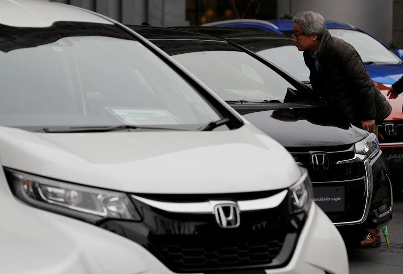 A man looks around Honda cars in a showroom at the company's headquarters in Tokyo