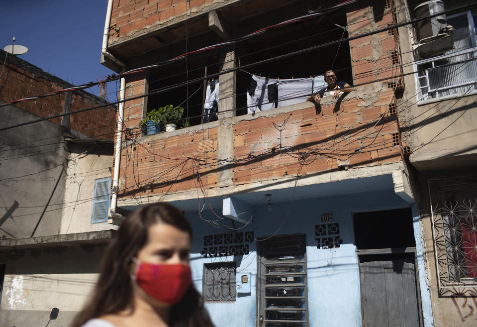 A resident watches from his home's window as water utility workers from CEDAE disinfect the streets in an effort to curb the spread of the new coronavirus in the Mare Complex slum of Rio de Janeiro, Brazil, Monday, May 4, 2020. (AP Photo/Silvia Izquierdo)