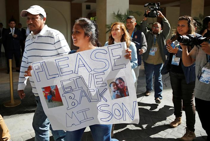 Elsa Ortiz holds a placard with pictures of her son, Anthony David Tobar, who was then at a shelter in Houston. (Photo: Luis Echeverria/Reuters)