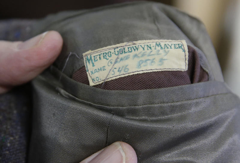 """This photo taken Monday, Dec. 2, 2013, shows the grey wool suit Gene Kelly wore in the movie """"Singin' in the Rain"""" is displayed at at Heritage Auctions in Dallas. Kelly's suit was purchased Thursday, Dec. 12, 2013, by the theme restaurant Planet Hollywood International for more than $106,000. Kelly wore the suit for the soggy featured dance in the 1952 movie musical. (AP Photo/LM Otero)"""