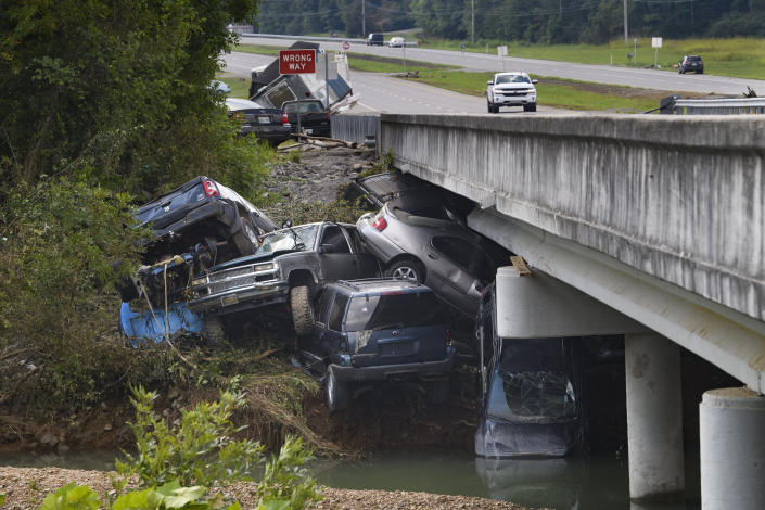 Cars are stacked on top of each other on the banks of Blue Creek being swept up in flood water, Monday, Aug. 23, 2021, in Waverly, Tenn. Heavy rains caused flooding in Middle Tennessee days ago and have resulted in multiple deaths as homes and rural roads were washed away. (AP Photo/John Amis)