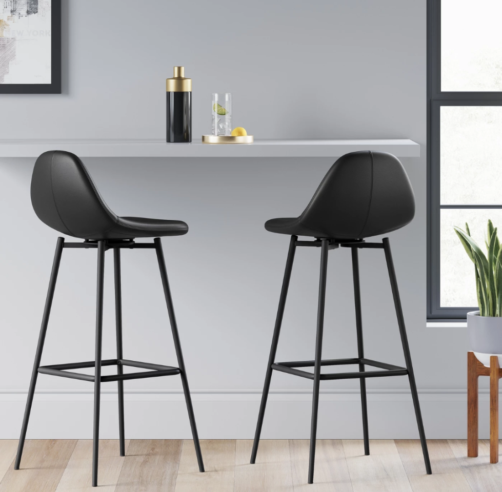 """<p><strong>Project 62™</strong></p><p>target.com</p><p><strong>$56.99</strong></p><p><a href=""""https://www.target.com/p/copley-upholstered-barstool-light-gray-project-62-153/-/A-52956577"""" target=""""_blank"""">BUY NOW</a></p><p>Sleek black faux leather and modern legs give these bar stools a sophisticated look.</p>"""