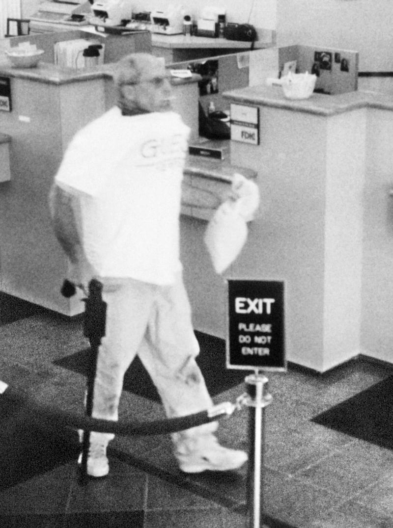 "FILE -  In this surveillance video image released Sept. 17, 2005, by the FBI, pizza deliveryman Brian Wells, of Erie, Pa., carries a plastic bag of cash after robbing the PNC bank, Aug. 28, 2003, at Summit Towne Centre in Erie.  Wells was killed when a bomb that was attached to a collar locked around his neck exploded after the robbery. Columbia Pictures comedy film ""30 Minutes or Less"" opens in theaters nationwide on Friday. Family members of Wells, say they will avoid the film that has a premise similar to the incident that killed Wells. (AP Photo/FBI photo via The Erie Times-News, File)"