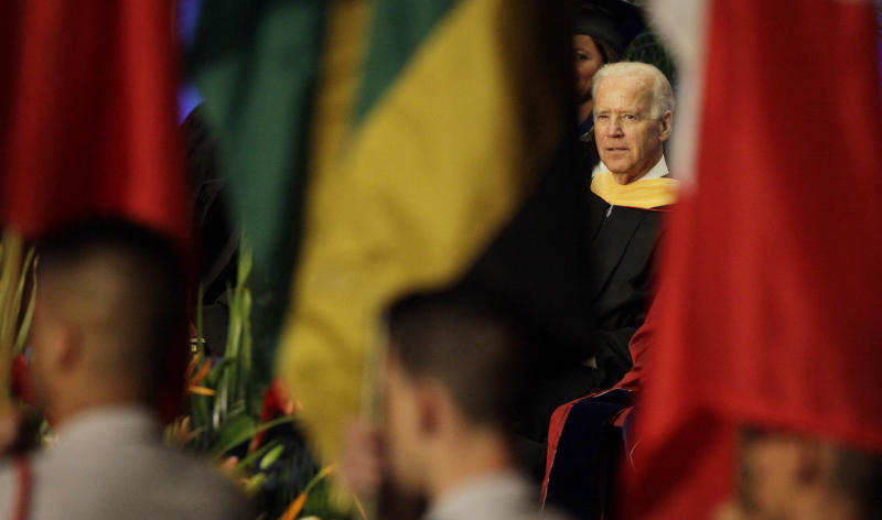 "A procession with International flags past as Vice President Joe Biden listens during a graduation ceremony at the Miami Dade College in Miami, Saturday, May 3,2014. Biden said a ""constant, substantial stream of immigrants"" is important to the American economy, urging citizenship for immigrants living in the U.S. illegally. (AP Photo/Javier Galeano)"