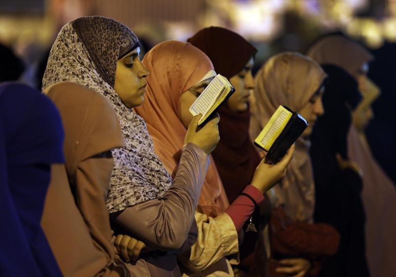 Supporters of Egypt's ousted President Mohammed Morsi read verses from Islam's holy book the Quran as they pray the Tarawih prayer, after the evening meal when Muslims break their fast during the Islamic month of Ramadan, in front of Cairo University, where protesters have installed their camp in Giza, southwest of Cairo, Egypt, late Wednesday, July 17, 2013. The European Union's top foreign policy official urged Egypt's interim leaders and supporters of the ousted Islamist president Wednesday to cooperate in a political process that moves the country toward democracy. But Mohammed Morsi's backers expanded their protests in Cairo, denouncing the new government and casting doubt on the prospects for reconciliation. (AP Photo/Hussein Malla)