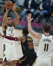 Indiana Pacers' Malcolm Brogdon (7) passes the ball over Cleveland Cavaliers' Isaac Okoro (35) to Domantas Sabonis (11) during the second half of an NBA basketball game Wednesday, March 3, 2021, in Cleveland. (AP Photo/Tony Dejak)