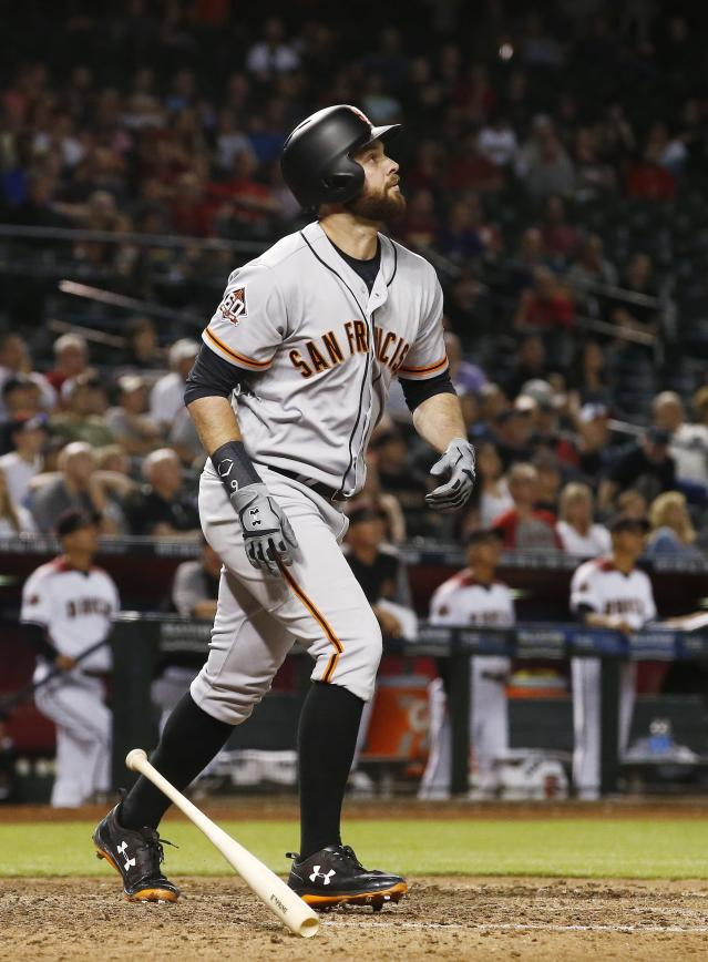 San Francisco Giants' Brandon Belt watches his two-run home run against the Arizona Diamondbacks during the 10th inning of a baseball game Wednesday, April 18, 2018, in Phoenix. (AP Photo/Ross D. Franklin)