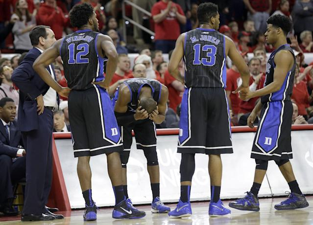 Duke's Rasheed Sulaimon holds his head during a timeout against North Carolina State late in the second half of an NCAA college basketball game in Raleigh, N.C., Sunday, Jan. 11, 2015. Coach Mike Krzyzewski, left, Justise Winslow (12), Matt Jones (13) and Quinn Cook, right, huddle. North Carolina State won 87-75. (AP Photo/Gerry Broome)