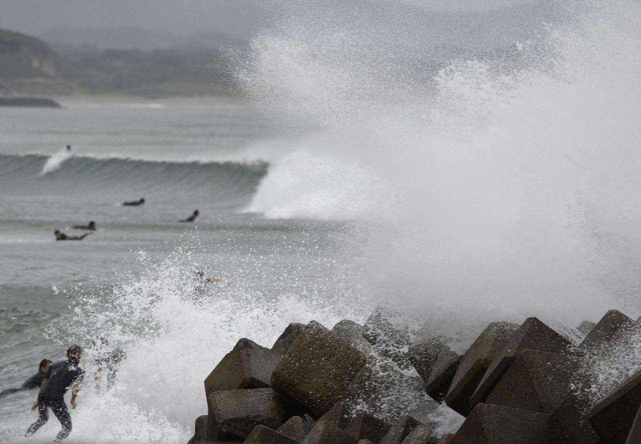 Waves crash as Typhoon Vongfong approaches Japan's main islands while surfers try to ride  a wave at Eguchihama Beach in Hioki, Kagoshima prefecture, in this photo taken by Kyodo October 12, 2014. Typhoon Vongfong battered the southern Japanese island of Okinawa on Sunday, injuring 31 people and knocking out power before losing intensity and getting downgraded to a tropical storm. Mandatory credit. REUTERS/Kyodo (JAPAN - Tags: DISASTER ENVIRONMENT) ATTENTION EDITORS - FOR EDITORIAL USE ONLY. NOT FOR SALE FOR MARKETING OR ADVERTISING CAMPAIGNS. THIS IMAGE HAS BEEN SUPPLIED BY A THIRD PARTY. IT IS DISTRIBUTED, EXACTLY AS RECEIVED BY REUTERS, AS A SERVICE TO CLIENTS. MANDATORY CREDIT. JAPAN OUT. NO COMMERCIAL OR EDITORIAL SALES IN JAPAN. YES