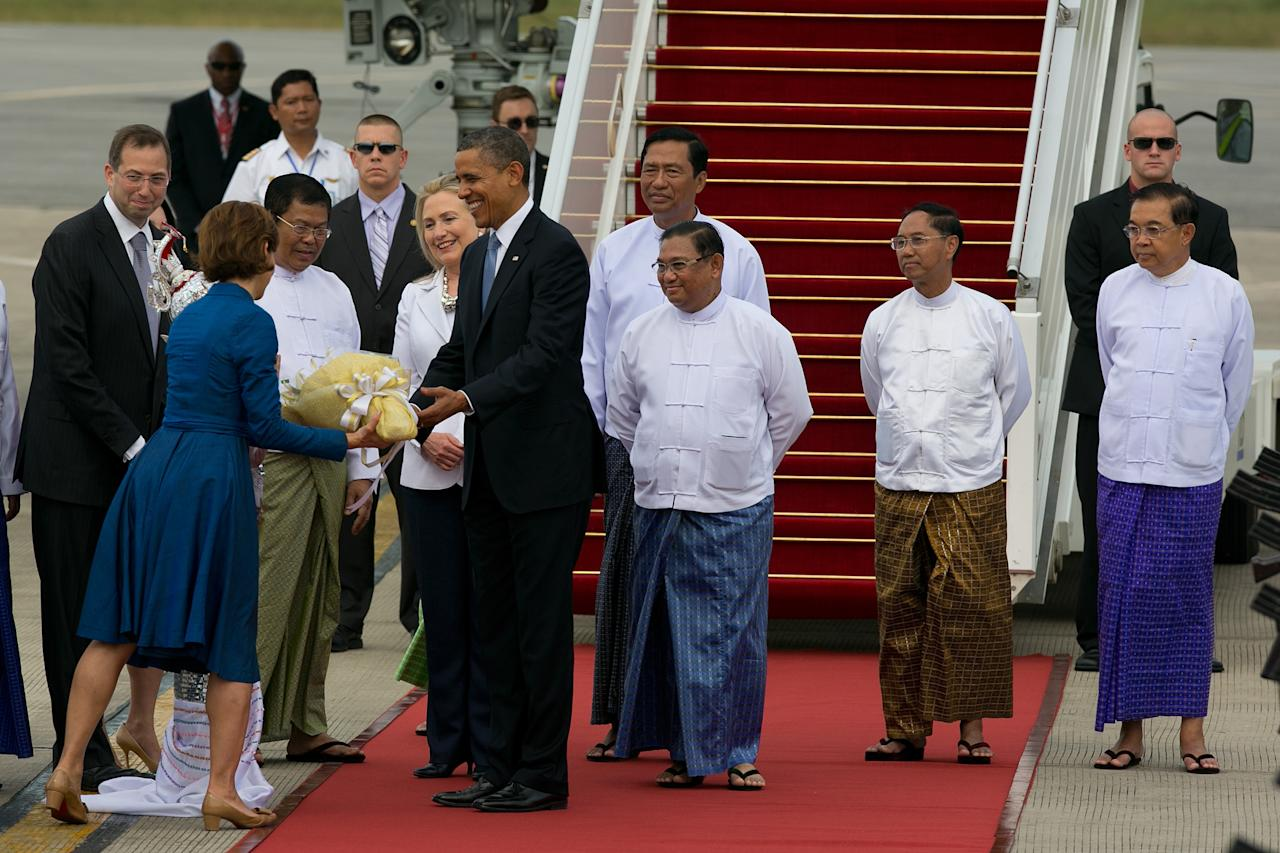 YANGON, MYANMAR - NOVEMBER 19: US President Barack Obama alongside Secretary of State Hilary Clinton (6th-R) and Burmese Foreign minister Wunna Maung Lwin (3rd-R) are greeted with flowers as they arrive at Yangon International airport during a historical visit to the country on November 19, 2012 in Yangon, Myanmar. Obama is the first US President to visit Myanmar while on a four-day tour of Southeast Asia that also includes Thailand and Cambodia. (Photo by Paula Bronstein/Getty Images)