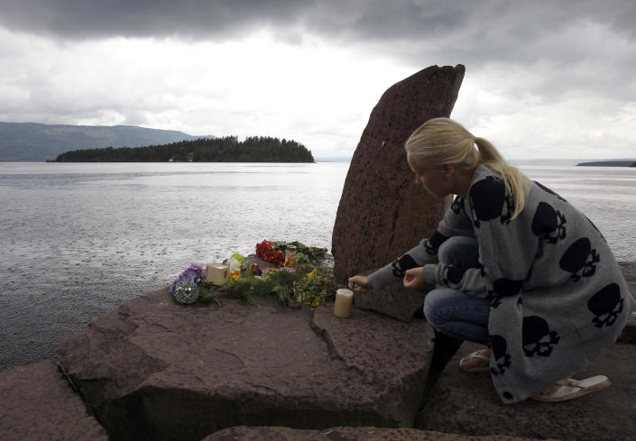 FILE - In this Sunday, July 24, 2011 file photo, a female lights a candle at a makeshift memorial to victims of the bombing and shooting attacks, opposite Utoya island, Norway. At 3.25 p.m. on July 22, 2021, a ray of sun should have illuminated the first of 77 bronze columns on a lick of land opposite Utoya island outside Oslo. Over the next 3 hours and 8 minutes, it would have brushed each column in turn, commemorating every person killed by right-wing terrorist Anders Breivik. But on the ten-year anniversary of the terror, the memorial remains a construction site. (AP Photo/Frank Augstein, File)