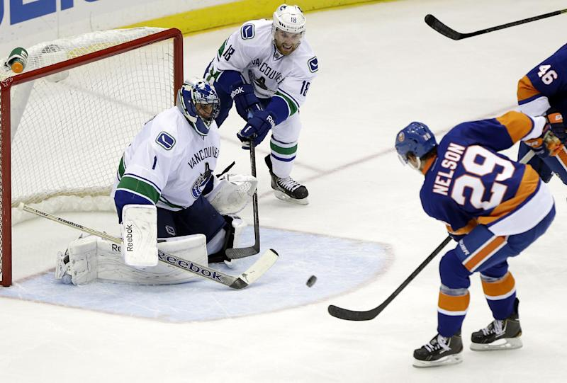Vancouver Canucks goalie Roberto Luongo (1) and Ryan Stanton (18) defend the goal as New York Islanders' Brock Nelson (29) shoots the puck during the second period of an NHL hockey game Tuesday, Oct. 22, 2013 in Uniondale, N.Y. (AP Photo/Frank Franklin II)