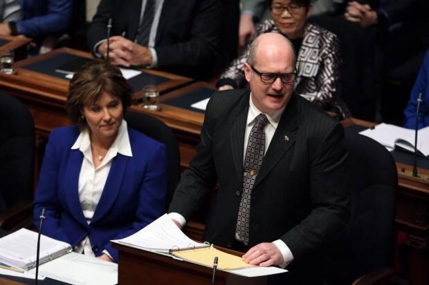 Premier Christy Clark looks on as then-finance minister Michael de Jong waits to deliver the provincial budget at Legislative Assembly in Victoria on Feb. 21, 2017. De Jong told Clark about a rise in reports of suspicious cash transactions in Lower Mainland casinos in 2015, leading to the creation of an integrated task force.
