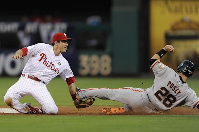 Philadelphia Phillies second baseman Chase Utley, left, tags San Francisco Giants' Buster Posey for the final out in the second inning inning of a baseball game on Monday, July 21, 2014, in Philadelphia. (AP Photo/Michael Perez)