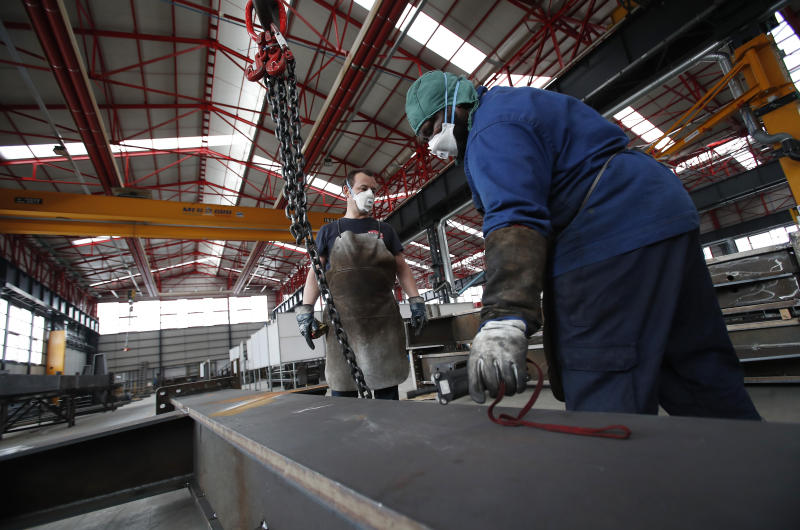 Workers wear face masks at MAP, a factory operating in design, manufacture and installation of steel structures for civil and industrial use, in Corsico, near Milan, Italy, Wednesday, May 6, 2020. Italy began stirring again after the coronavirus shutdown, with 4.4 million Italians able to return to work and restrictions on movement eased in the first European country to lock down in a bid to stem COVID-19 infections. (AP Photo/Antonio Calanni)