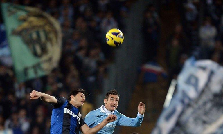 Lazio's forward Miroslav Klose (R) jumps for the ball with Inter Milan's defender Andrea Ranocchia on December 15, 2012