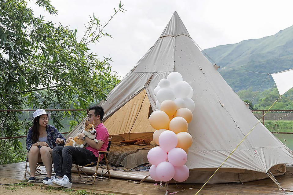 A young couple with their dog spend their time outside an Indiana-style tent at We Camp, a glamping site located in Yuen Long, Hong Kong on Aug. 19, 2021. From the Great Wall to the picturesque Kashmir valley, Asia's tourist destinations are looking to domestic visitors to get them through the COVID-19 pandemic's second year. With international travel heavily restricted, foreign tourists can't enter many countries and locals can't get out. The difficulty of traveling abroad has made glamping, or glamourous camping, popular in Hong Kong. (AP Photo/Matthew Cheng)