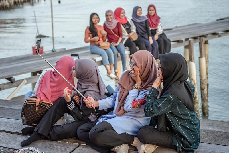 Muslim women enjoy the sunset in one of the Clan Jetties villages, in George Town, Penang Island, Malaysia, in January 2019. | Oleksandr Rupeta—NurPhoto via Getty Images