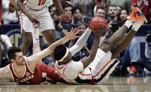 Mississippi guard Terence Davis, right, comes up with the ball after battling Alabama's Riley Norris, left, in the second half of an NCAA college basketball game at the Southeastern Conference tournament Thursday, March 14, 2019, in Nashville, Tenn. Alabama won 62-57. (AP Photo/Mark Humphrey)