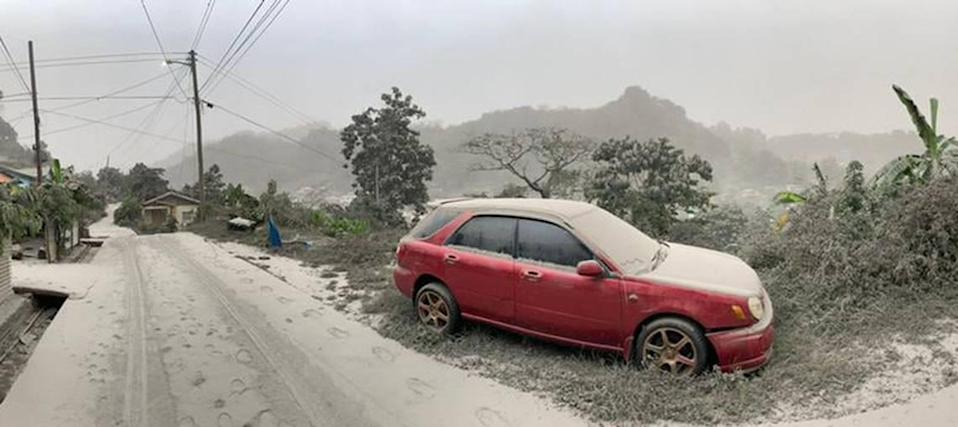 This April 10, 2021, handout image courtesy of the UWI Seismic Research Center shows a car and road covered in ash after the April 9 eruption of the La Soufriere Volcano. La Soufriere erupted for the first time in 42 years on the Caribbean island of Saint Vincent, prompting thousands of people to evacuate, seismologists said.