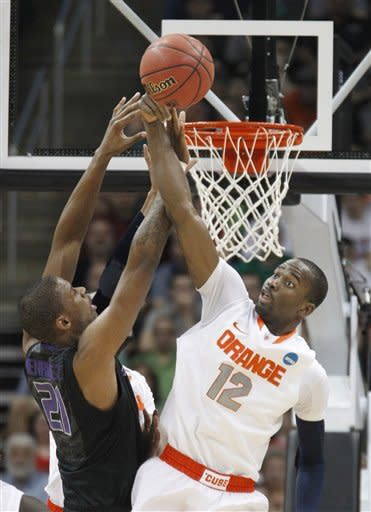 Syracuse's Baye Keita (12) blocks a shot by Kansas State's Jordan Henriquez in the first half of an East Regional NCAA tournament third-round college basketball game on Saturday, March 17, 2012 in Pittsburgh. (AP Photo/Keith Srakocic)