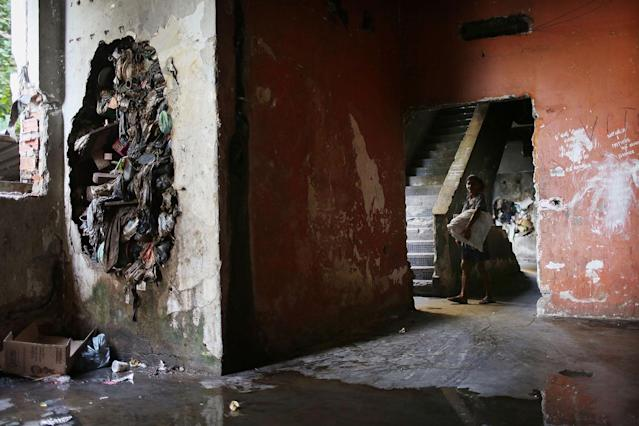 <p>A resident walks in one of the occupied buildings in the Mangueira favela, May 4, 2017, in Rio de Janeiro. (Photo: Mario Tama/Getty Images) </p>