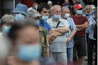 People wait in line to receive a COVID-19 vaccine at a mobile vaccination center, in Bucharest